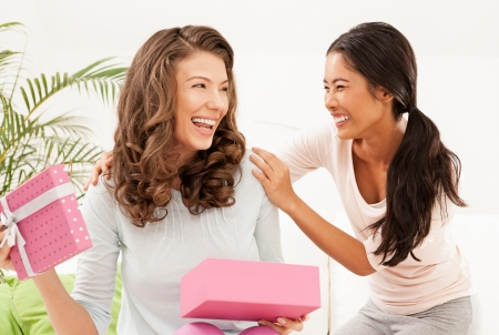 Two friends sharing the happy moments of opening a birthday present  Stock Photo