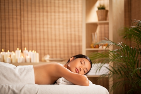 Young Asian woman relaxing at a spa centre. Stock Photo