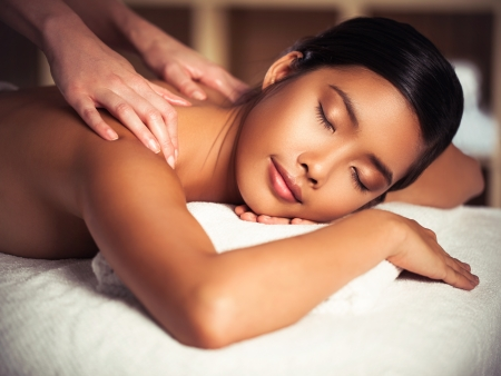 bodycare: Asian woman enjoying a back massage at a spa centre.