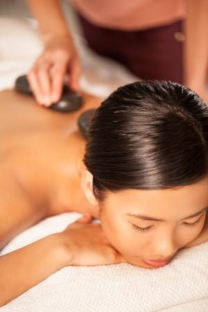 Asian woman enjoying a hot stone treatment. photo
