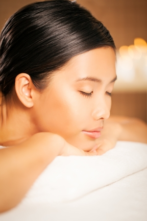 massage table: Asian woman waiting for a massage at a massage parlor.