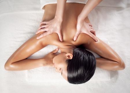 masajes relajacion: Mujer asiática que disfruta de un masaje de espalda en un centro de spa.