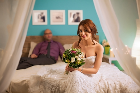 Smiling bride sitting on the bed in front of her husband. photo