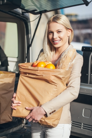 Smiling woman holding paper bags full of groceries in front of her car  Stock Photo