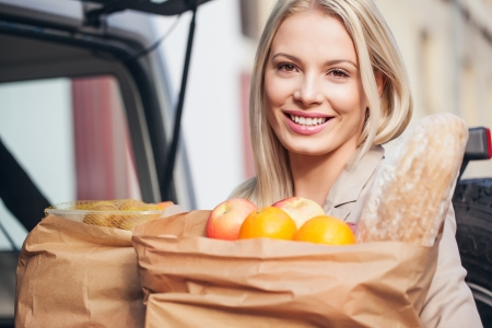 Smiling woman holding paper bags full of groceries  photo