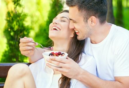 pareja comiendo: Sonriente joven que introduce a su amante mujer en una ma�ana soleada en su jard�n