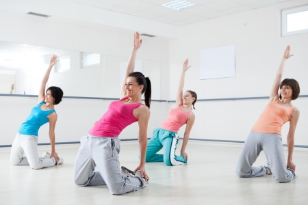 Group of young smiling women doing exercise on aerobic class at a fitness studio.