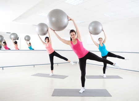 Young women doing exercise with Pilates ball in fitness gym  photo