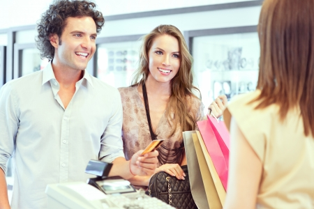 Un jeune couple de payer pour les vêtements qu'ils ont juste acheté.