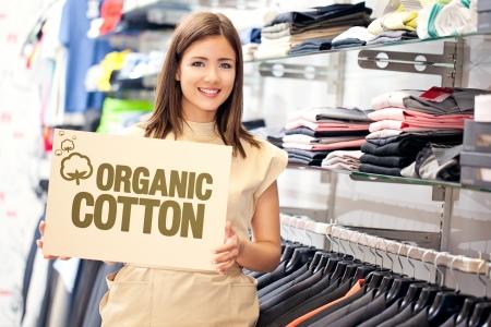 organic cotton: Una bella assistente di negozio detiene il segno di cotone organico.