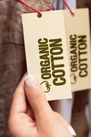 organic cotton: A woman holding the organic cotton label on a pair of cotton pants.