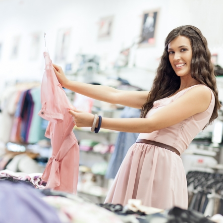 likes: A beautiful young woman holding a shirt she really likes. Stock Photo