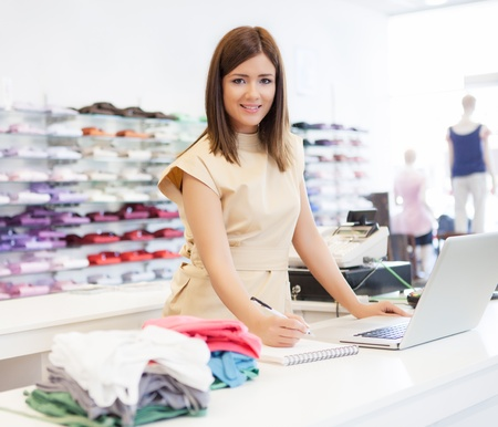 clothing stores: A shop assistant standing at the checkout desk. Stock Photo