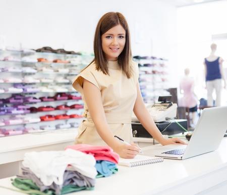 Un assistente di negozio in piedi al banco cassa.