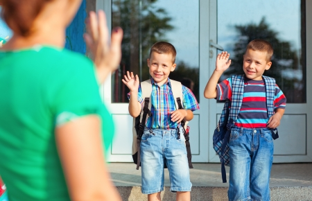 school backpack: Dos hermanos que agita de nuevo a su madre en su primer día en la escuela.