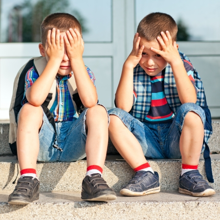 Two worried schoolboys sitting in front of their school. photo