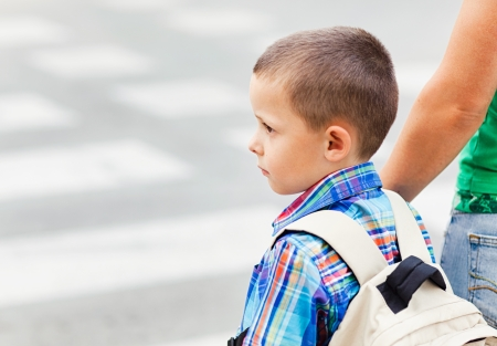 crossing a street: A cute little boy and his mother waiting to cross the street on their way to school.