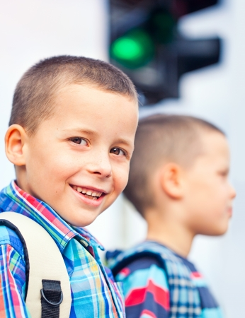 crossing: Two boys waiting to cross the street on their way to school. Stock Photo