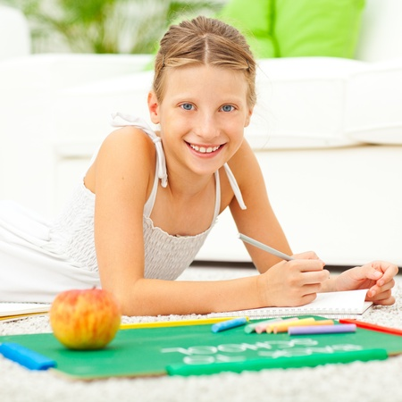 A smiling schoolgirl lying on the floor and doing homework at home. photo