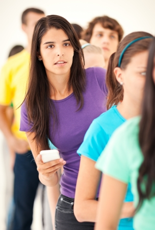 impatient: A beautiful young woman showing impatience while standing in a long queue.