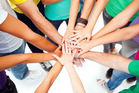 adolescencia: Un grupo de personas que muestran su unidad poniendo su manos una encima de la otra.