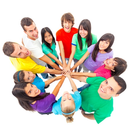people looking up: A group of cheerful people showing their unity by putting their hands one on top of the other.