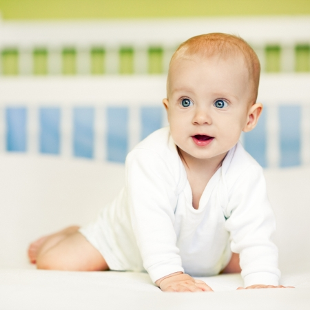 crawling baby: Cute baby boy looking surprisedly at something.