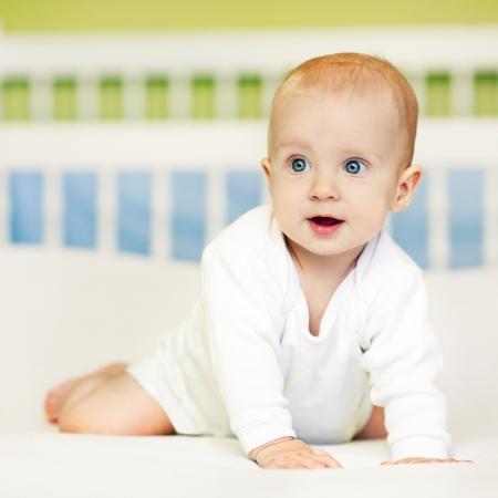 bebe gateando: Niño lindo mirando surprisedly en algo.