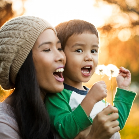 asian child: Young mother and her cute son blowing dandelion flowers together.