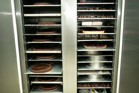refrigerator with food: Large cake-shop refrigerator full of cakes.