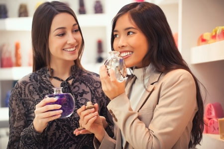 Two smiling women smelling the fragrance of different aromatherapy oils. photo
