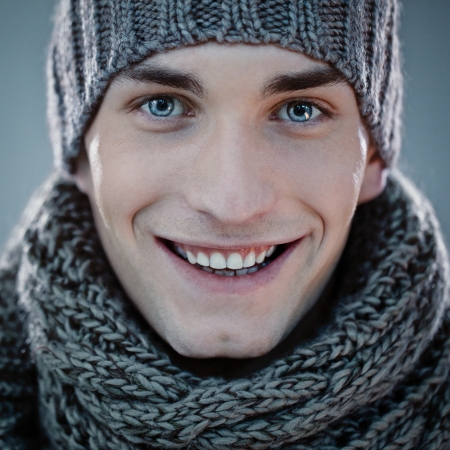 Handsome young man wearing a knit hat and a scarf. photo