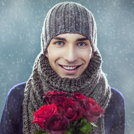 Handsome young man in winter clothes holding a bunch of red roses. photo