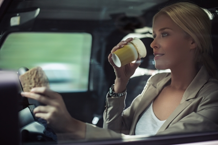drinking and driving: Beautiful mid-adult woman heading to work in her car. Stock Photo