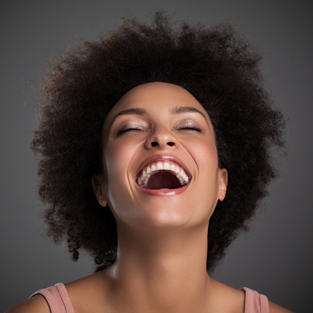 black hair: Portrait of a beautiful African woman laughing.
