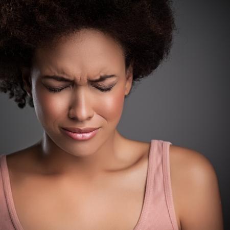 mujer llorando: Joven mujer africana vive un momento doloroso.