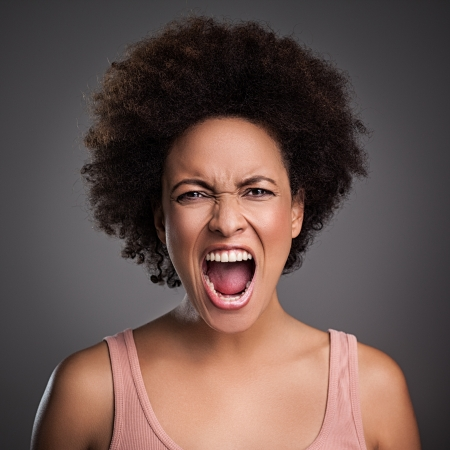 afro hair: Young African woman shouting angrily.