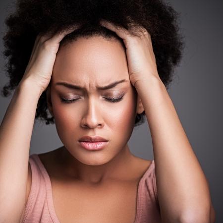 mujer decepcionada: Joven mujer africana que sufre de un dolor de cabeza terrible.