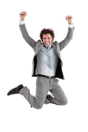 businessman jumping: Smiling Caucasian businessman jumping for joy. Stock Photo