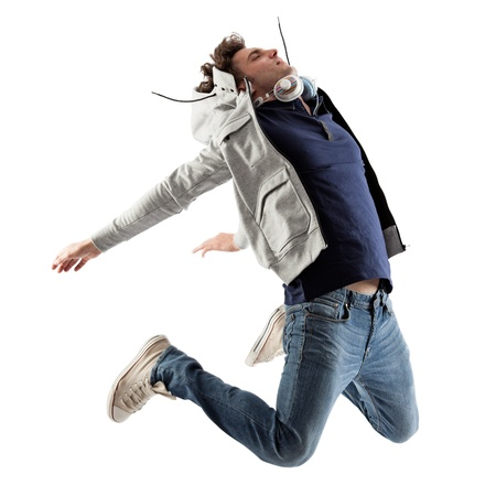 jump: Cool Caucasian man with headphones around his neck jumping.