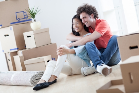 mixed race people: Young multi-ethnic couple resting while moving into their new home.