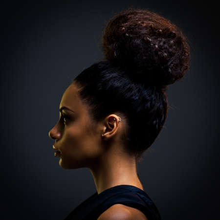 Glamorous young African woman's profile agaisnt a dark background. photo