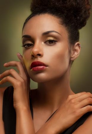bollos: Glamorous joven mujer africana que toca suavemente su cara.