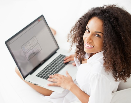 Smiling African woman working on her laptop at home. photo