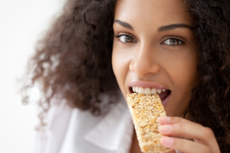 cereal bar: Smiling African woman eating a heathy cereal snack bar. Stock Photo
