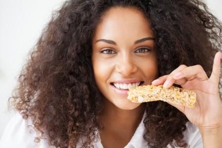 barra de cereal: Mujer africana sonriente comer un snack bar heathy cereal. Foto de archivo