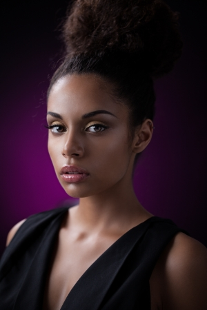 Portrait of a glamorous young African woman against a purple background.