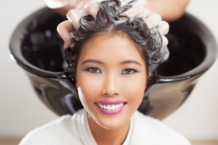 Smiling Asian woman having her hair washed at the hairdresser's. photo