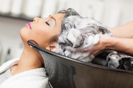 champu: Sonriente mujer asiática que se lava el pelo en la peluquería.