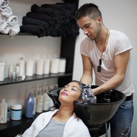 Smiling Asian woman having her hair washed at the hairdressers. photo
